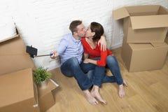 Junge glückliche amerikanische Paare, die auf dem Boden macht selfie Foto feiert das Bewegen in neues Haus oder in Wohnung sitzen stockfotografie