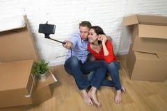 Junge glückliche amerikanische Paare, die auf dem Boden macht selfie Foto feiert das Bewegen in neues Haus oder in Wohnung sitzen lizenzfreies stockfoto