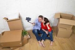 Junge glückliche amerikanische Paare, die auf dem Boden macht selfie Foto feiert das Bewegen in neues Haus oder in Wohnung sitzen stockfoto