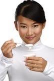 Junge glückliche asiatische Frau, die frischen Jogurt isst Lizenzfreie Stockfotos