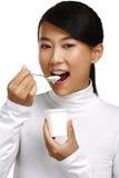Junge glückliche asiatische Frau, die frischen Jogurt isst Stockbild