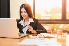 Junge glückliche asiatische Geschäftsfrau, die Kreditkarte und den Einkauf hält lizenzfreies stockbild