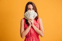 Junge glückliche attraktive Frau im roten Kleid, das hinter Bündel von sich versteckt lizenzfreies stockfoto