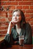 Junge glückliche blonde Frau in der grünen Bluse, die nahe Fenster gegen Wand des roten Backsteins am Café mit c-Kakaoglas sitzt Stockfotos