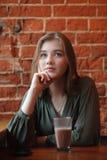 Junge glückliche blonde Frau in der grünen Bluse, die nahe Fenster gegen Wand des roten Backsteins am Café mit c-Kakaoglas sitzt Stockfotografie
