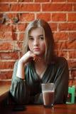 Junge glückliche blonde Frau in der grünen Bluse, die nahe Fenster gegen Wand des roten Backsteins am Café mit c-Kakaoglas sitzt Lizenzfreies Stockfoto