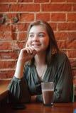 Junge glückliche blonde Frau in der grünen Bluse, die nahe Fenster gegen Wand des roten Backsteins am Café mit c-Kakaoglas sitzt Stockbilder