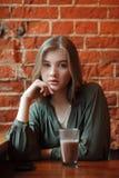 Junge glückliche blonde Frau in der grünen Bluse, die nahe Fenster gegen Wand des roten Backsteins am Café mit c-Kakaoglas sitzt Lizenzfreie Stockfotografie