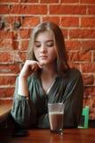 Junge glückliche blonde Frau in der grünen Bluse, die nahe Fenster gegen Wand des roten Backsteins am Café mit c-Kakaoglas sitzt Lizenzfreies Stockbild