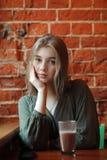 Junge glückliche blonde Frau in der grünen Bluse, die nahe Fenster gegen Wand des roten Backsteins am Café mit c-Kakaoglas sitzt Lizenzfreie Stockbilder