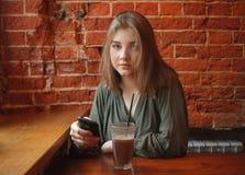 Junge glückliche blonde Frau in der grünen Bluse, die nahe Fenster gegen Wand des roten Backsteins am Café mit dem c-Kakaoglas si Stockbild