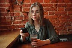 Junge glückliche blonde Frau in der grünen Bluse, die nahe Fenster gegen Wand des roten Backsteins am Café mit dem Kakaoglas sims Stockbild
