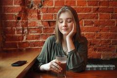 Junge glückliche blonde Frau in der grünen Bluse, die nahe Fenster gegen Wand des roten Backsteins am Café mit Kakaoglas sitzt Stockfoto
