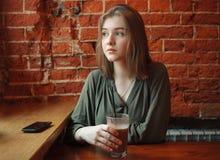 Junge glückliche blonde Frau in der grünen Bluse, die nahe Fenster gegen Wand des roten Backsteins am Café mit Kakaoglas sitzt Lizenzfreies Stockbild