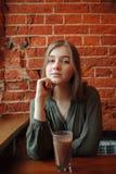 Junge glückliche blonde Frau in der grünen Bluse, die nahe Fenster gegen Wand des roten Backsteins am Café mit Kakaoglas sitzt Stockbild