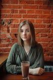 Junge glückliche blonde Frau in der grünen Bluse, die nahe Fenster gegen Wand des roten Backsteins am Café mit Kakaoglas sitzt Stockfotos