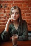 Junge glückliche blonde Frau in der grünen Bluse, die nahe Fenster gegen Wand des roten Backsteins am Café mit Kakaoglas sitzt Stockbilder