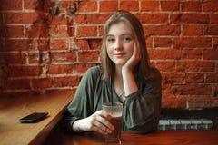 Junge glückliche blonde Frau in der grünen Bluse, die nahe Fenster gegen Wand des roten Backsteins am Café mit Kakaoglas sitzt Lizenzfreies Stockfoto