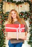 Junge glückliche blonde Frau, die Weihnachtsgeschenke hält Stockfotos