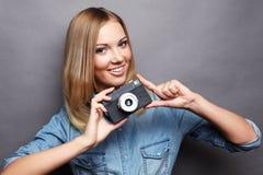 Junge glückliche blonde Frau mit Weinlesekamera Stockbild