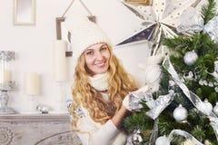 Junge glückliche blonde Frau nahe dem Weihnachtsbaum Lizenzfreie Stockfotografie
