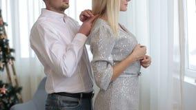 Junge glückliche Blondine, die ihren Ehemann im Weihnachten verzierten Raum umarmen inside Porträt stock video footage