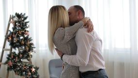 Junge glückliche Blondine, die ihren Ehemann im Weihnachten verzierten Raum umarmen inside Porträt stock footage