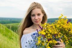 Junge glückliche Braut, die Blumenstrauß von blühenden gelben Blumen in der Landschaft hält Bild des schönen glücklichen Mädchens Stockbild