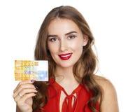 Junge glückliche Brunettefrau hält 10 Schweizer Franken Stockfoto