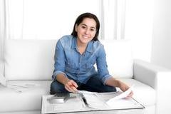 Junge glückliche Couch-Buchhaltungsbank der Frau zu Hause und Geschäftspapiere Lizenzfreie Stockfotografie
