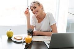Junge glückliche Dame entfernen Gläser und Schauenkamera in der Küche Lizenzfreie Stockfotografie