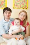 Junge glückliche Familie, die auf Sofa sitzt lizenzfreie stockfotografie