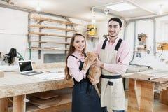 Junge glückliche Familie, die an der Tischlerwerkstatt arbeitet stockfotografie