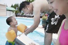 Junge glückliche Familie, die sich im Urlaub durch das Pool entspannt lizenzfreies stockfoto