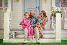 Junge glückliche Familie, die Spaß im Hof des Sommerhauses hat stockbilder
