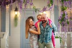 Junge glückliche Familie, die Spaß im Hof des Sommerhauses hat lizenzfreies stockbild