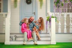 Junge glückliche Familie, die Spaß im Hof des Sommerhauses hat stockfotografie