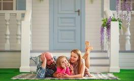 Junge glückliche Familie, die Spaß im Hof des Sommerhauses hat lizenzfreie stockfotografie