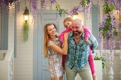Junge glückliche Familie, die Spaß im Hof des Sommerhauses hat lizenzfreie stockbilder