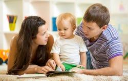 Junge glückliche Familie mit Babysohn-Lesekindern Lizenzfreies Stockfoto