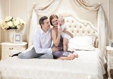 Junge glückliche Familie mit einem Baby auf Bett Lizenzfreies Stockbild