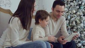 Junge glückliche Familie unter Verwendung der Tablette, die auf dem Sofa sitzt stock video