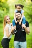 Junge glückliche Familie von drei den Spaß habend zusammen im Freien Recht kleine Tochter auf ihrer Vaterrückseite Tragende Tocht Lizenzfreies Stockfoto