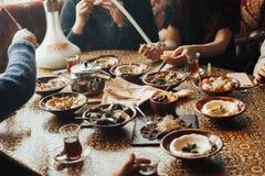 Junge glückliche Firma von Leuten isst der Libanon-Lebensmittel und smokinh shisha Der Libanon-Küche lizenzfreies stockbild
