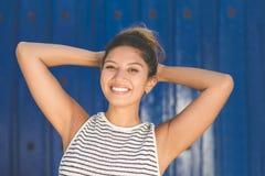 Junge glückliche Frau auf blauem Hintergrundhändchenhalten über Kopf Stockbilder
