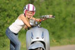 Junge glückliche Frau auf dem Roller im Freien Lizenzfreies Stockfoto