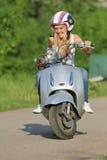 Junge glückliche Frau auf dem Roller im Freien Lizenzfreie Stockbilder