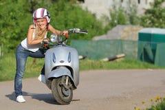 Junge glückliche Frau auf dem Roller im Freien Stockfotografie