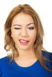 Junge glückliche Frau blinkt ihr Auge Lizenzfreies Stockfoto