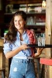 Junge glückliche Frau an der Barholding trinkt auf Behälter Lizenzfreies Stockbild